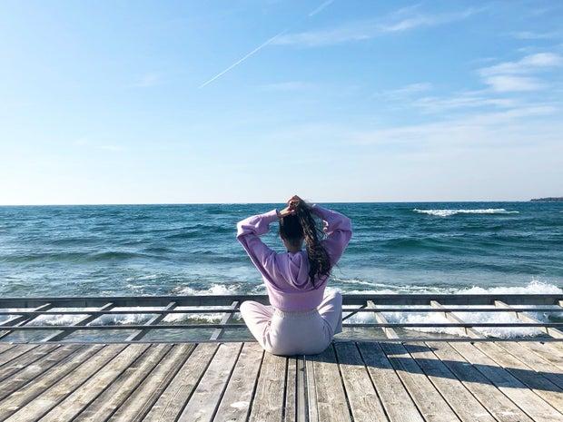 woman sitting on boardwalk facing ocean