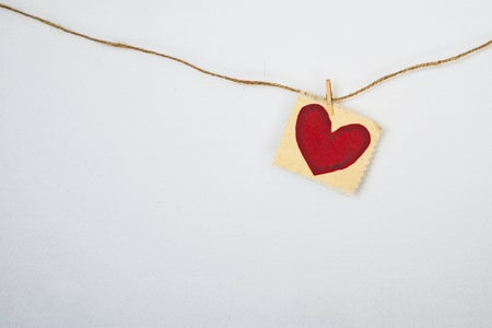 a little read heart attached with a clothespin to a horizontal piece of string against a gray wall