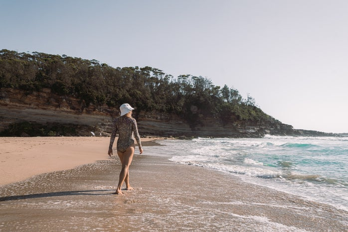 Woman in a long-sleeved body/swim suit walking on the beach.