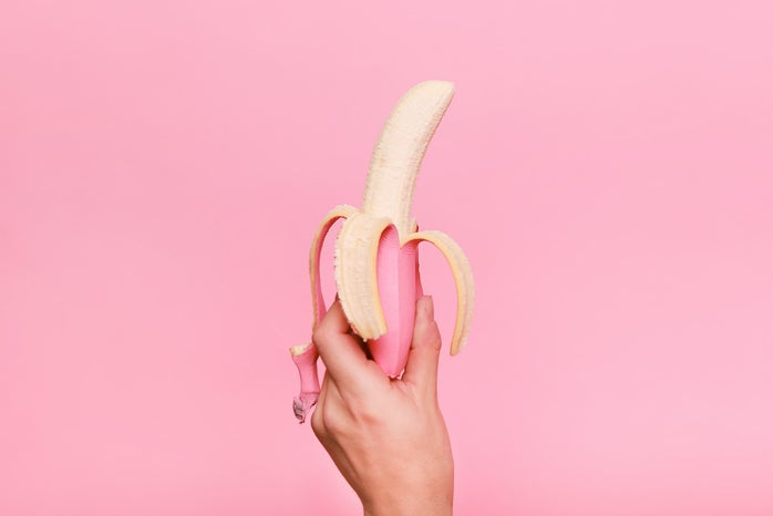 hand holding up a peeled banana in front of a pink background
