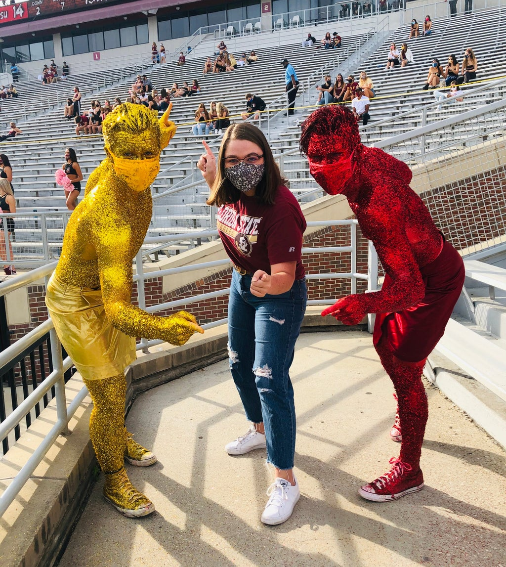 a girl standing between two guys who are covered in gold and garnet glitter