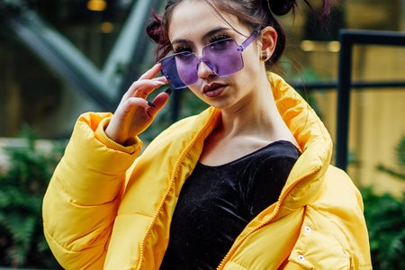 Bristol uk woman in yellow puffer coat and purple sunglasses bristol fashion
