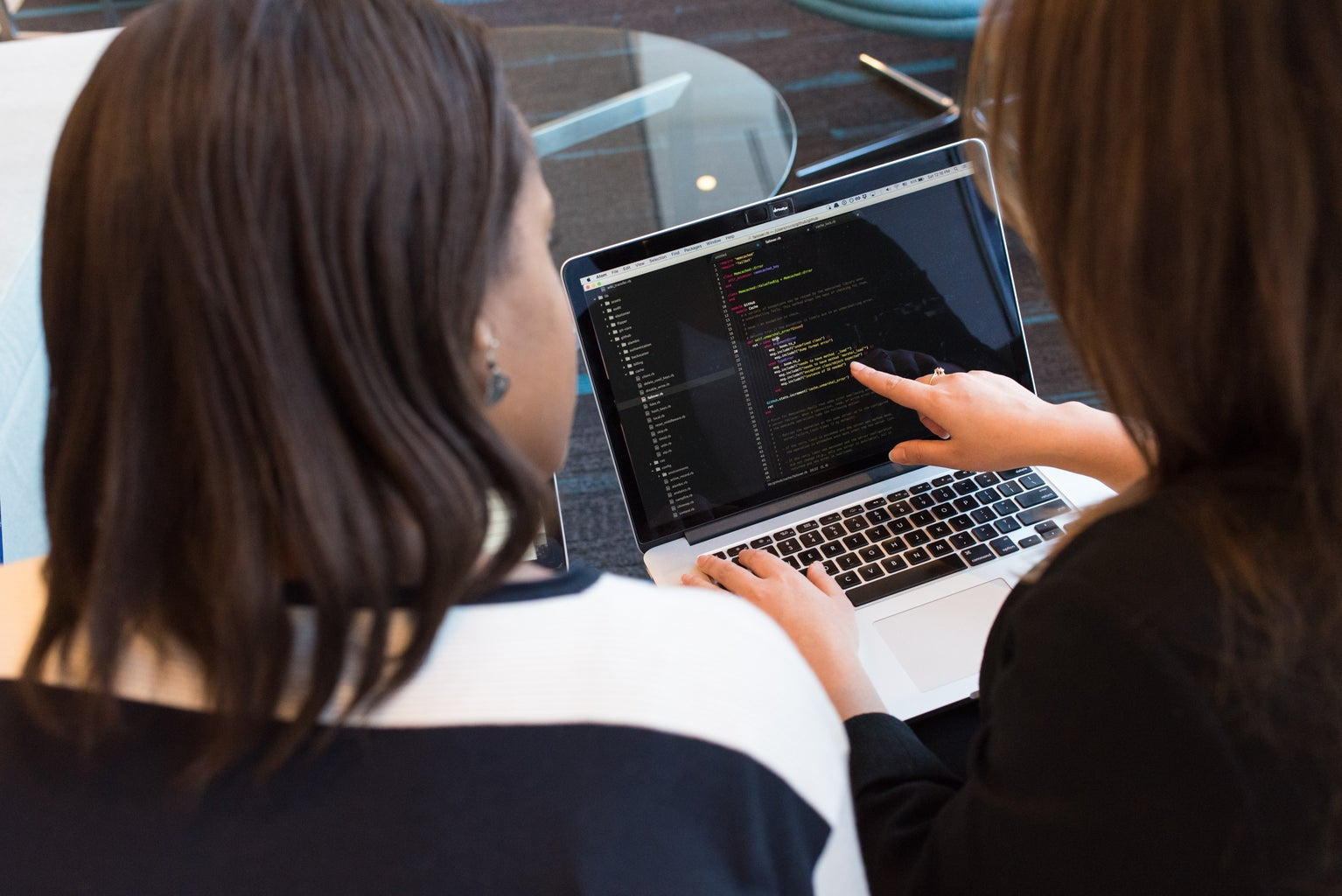 Two women looking at computer with code