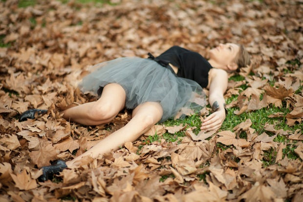 woman in grey dress lying on dried leaves