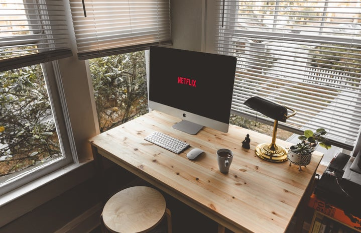 Netflix is displayed on a desktop computer on a table in an aesthetic office.