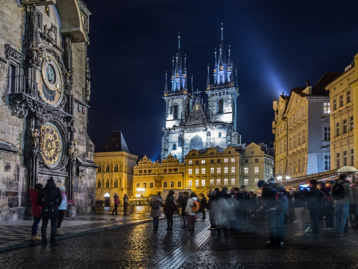 Prague courtyard with a group of pedestrians standing in the square, and white lights lighting up a building in the background.