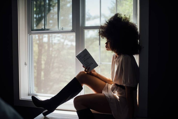Woman reading on window ledge