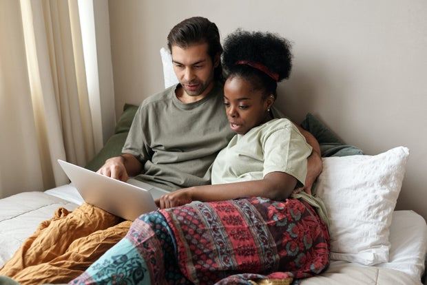 a couple looking at a computer screen cozy under the blankets