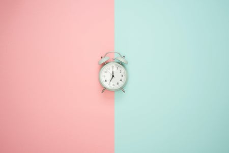 silver alarm clock on a pink and blue background