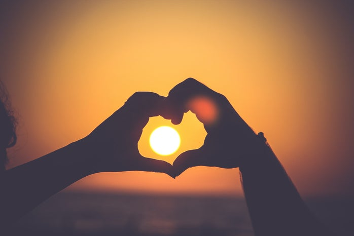 Hands in the shape of a heart around the sun