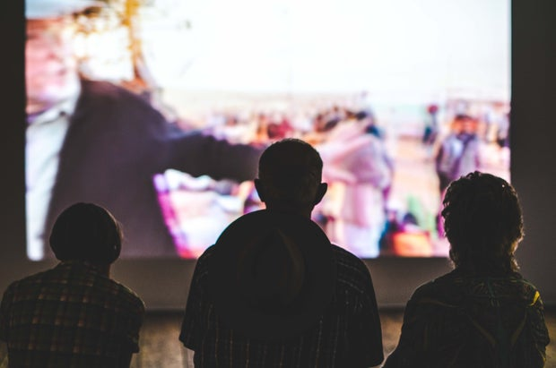 3 people watching TV on projector screen