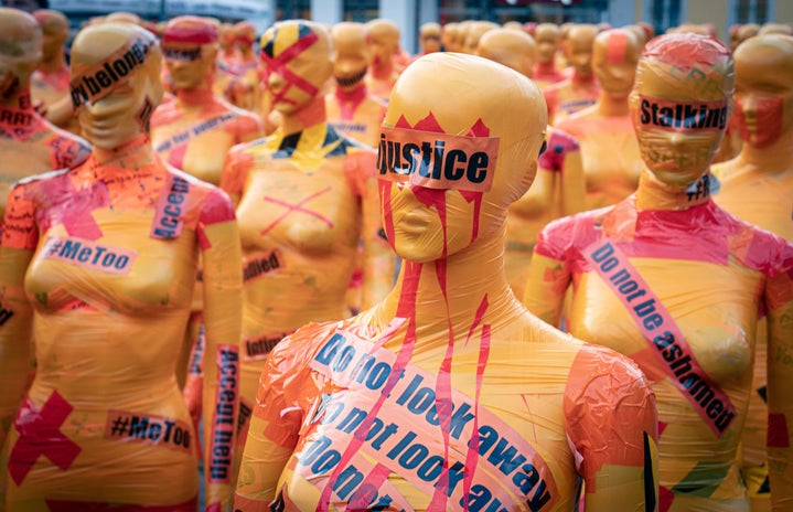 Mannequins covered with yellow tape and #MeToo