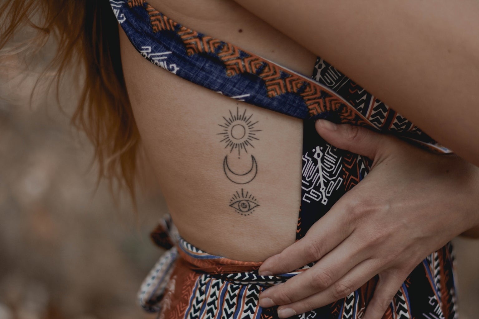 set of minimalistic tattoos on a person's ribcage