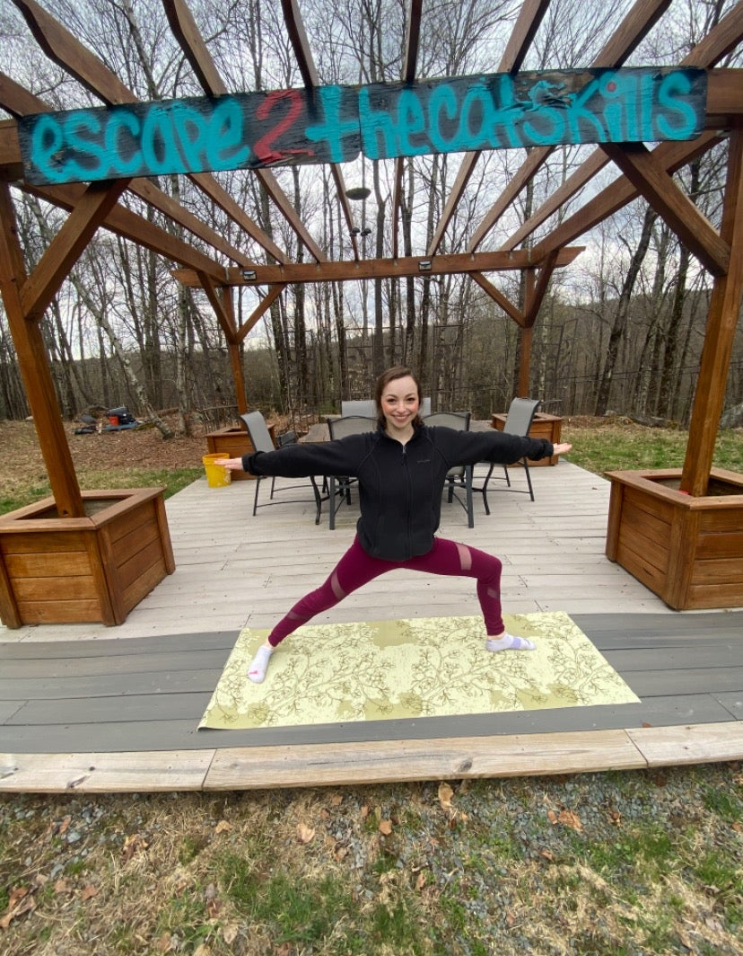 Camryn doing Warrior 2 in front of a patio in the Catskills