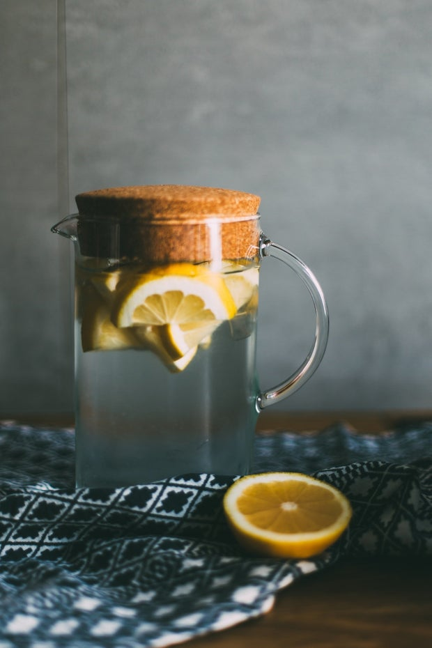 Lemons in water jug on table with cloth