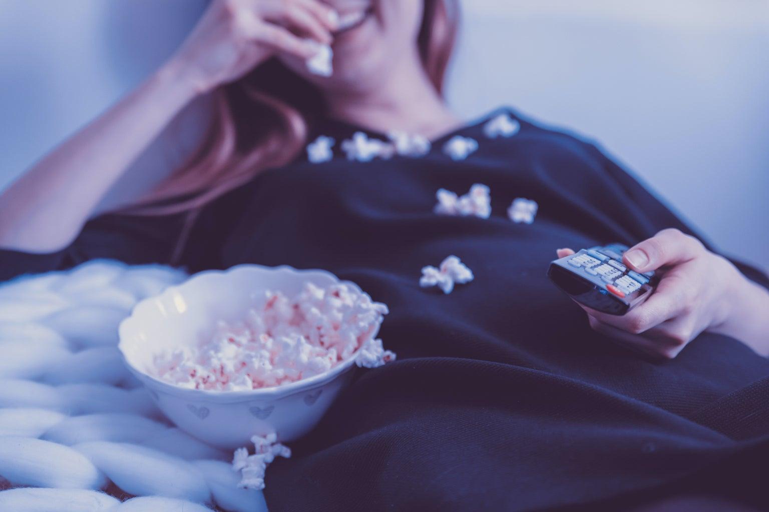 woman wearing black shirt eating popcorn