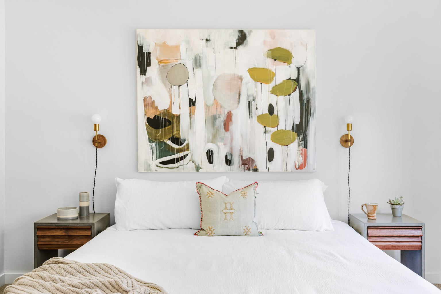 White bedspread with pink and olive green wall painting