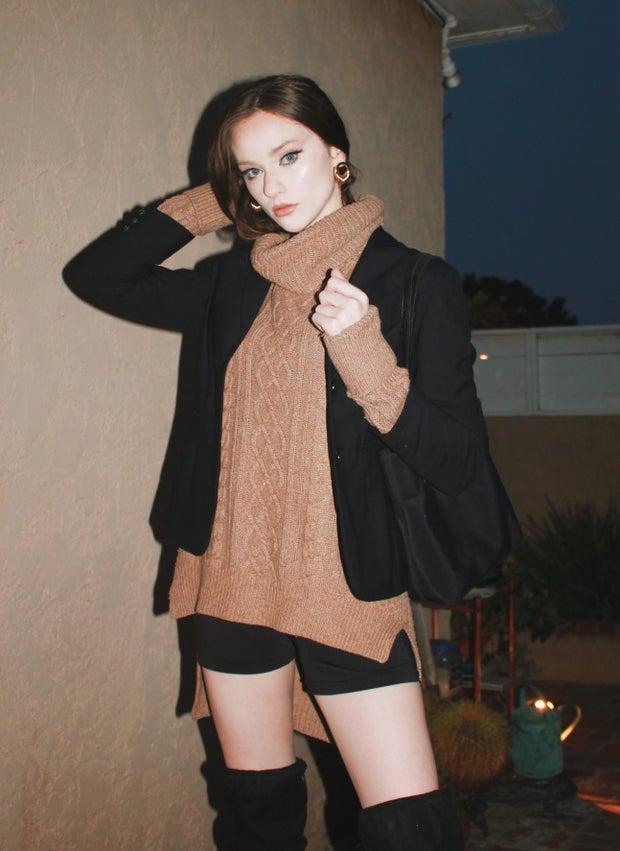young woman wearing tan turtleneck