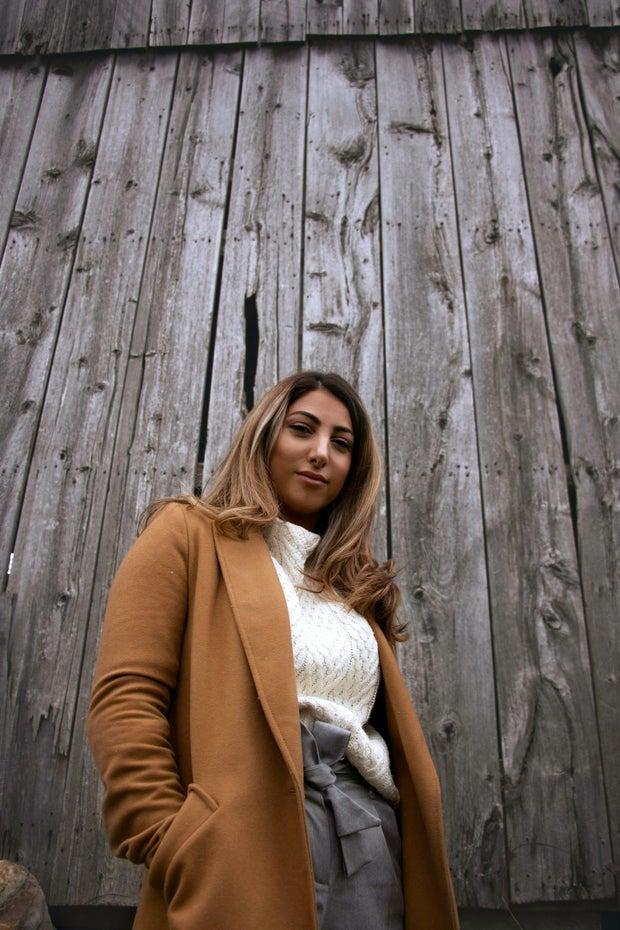 Woman in blazer against wooden background