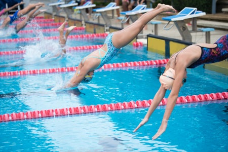 Swimmers diving off of blocks into a swimming pool