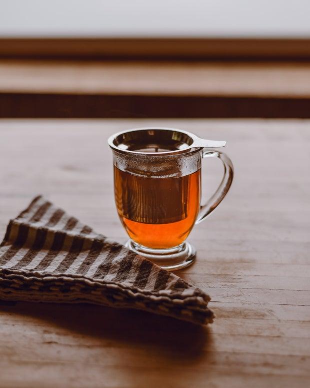 clear glass mug with tea steeping on brown table