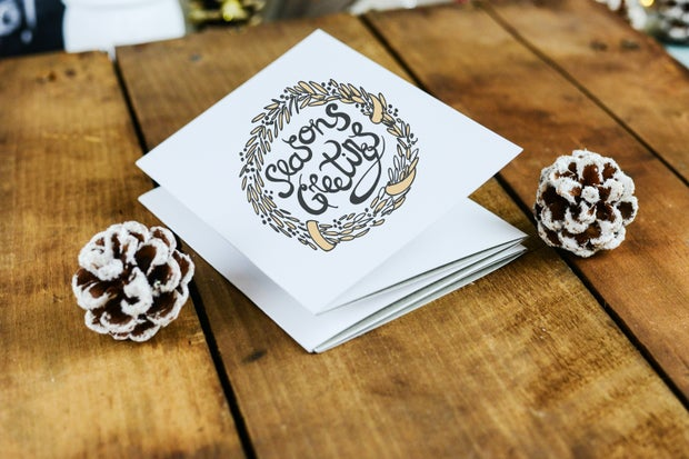 """white card with handwritten """"seasons greetings"""" message surrounded by pinecones"""