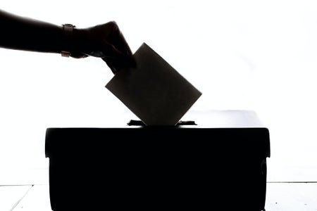 silhouette of a person putting a ballot in a box