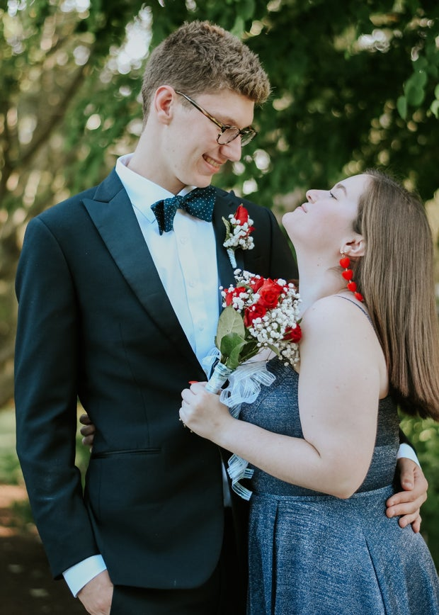 boyfriend and girlfriend together at prom, posing with flowers