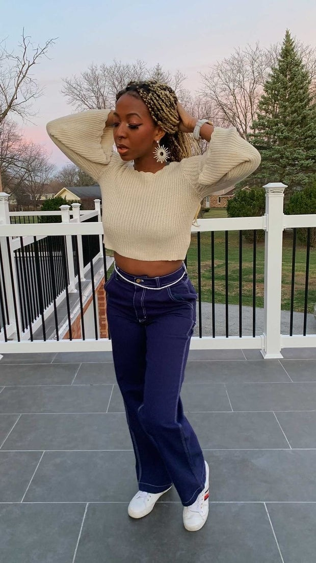 young woman wearing cream cropped sweater