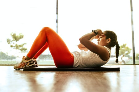 Woman exercising indoors on yoga mat