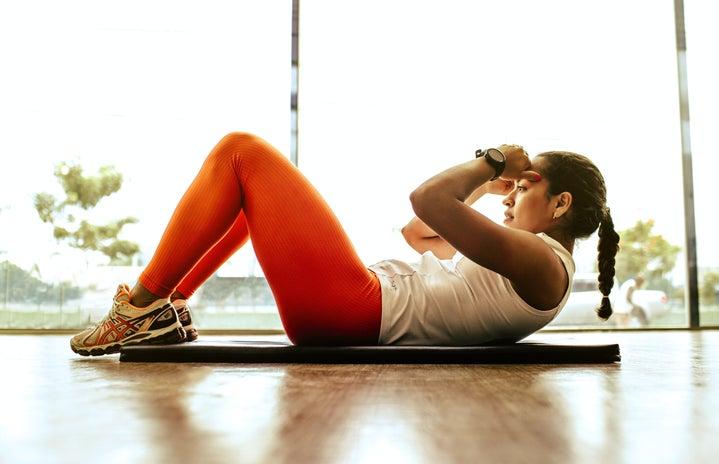 Woman exercising indoors on yoga mat