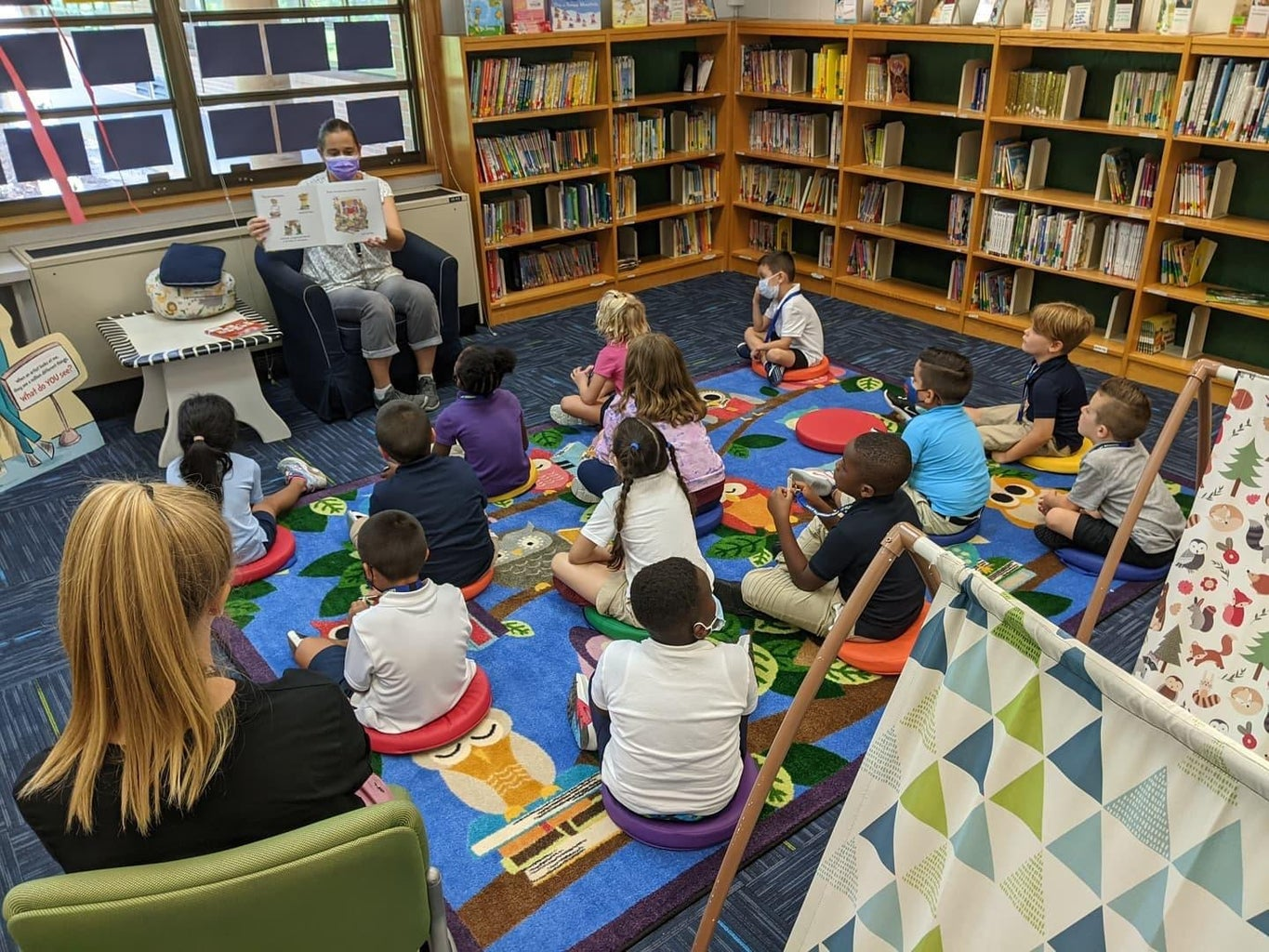 woman reading to group of kids