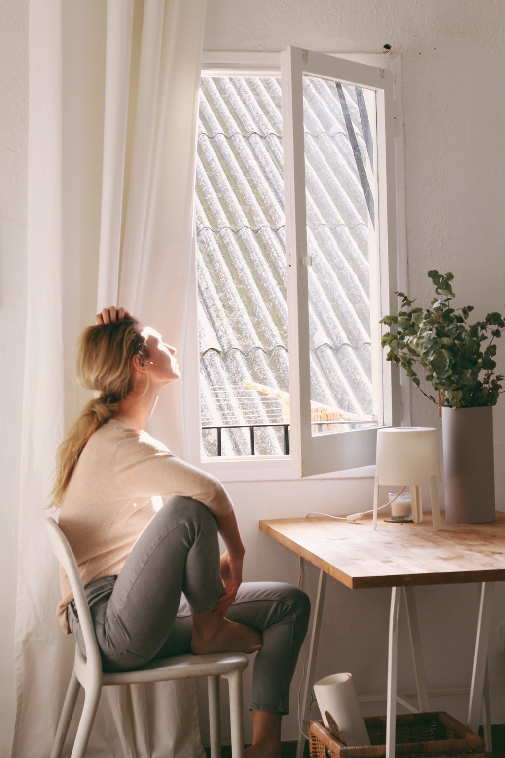 woman sitting on a chair next to a window