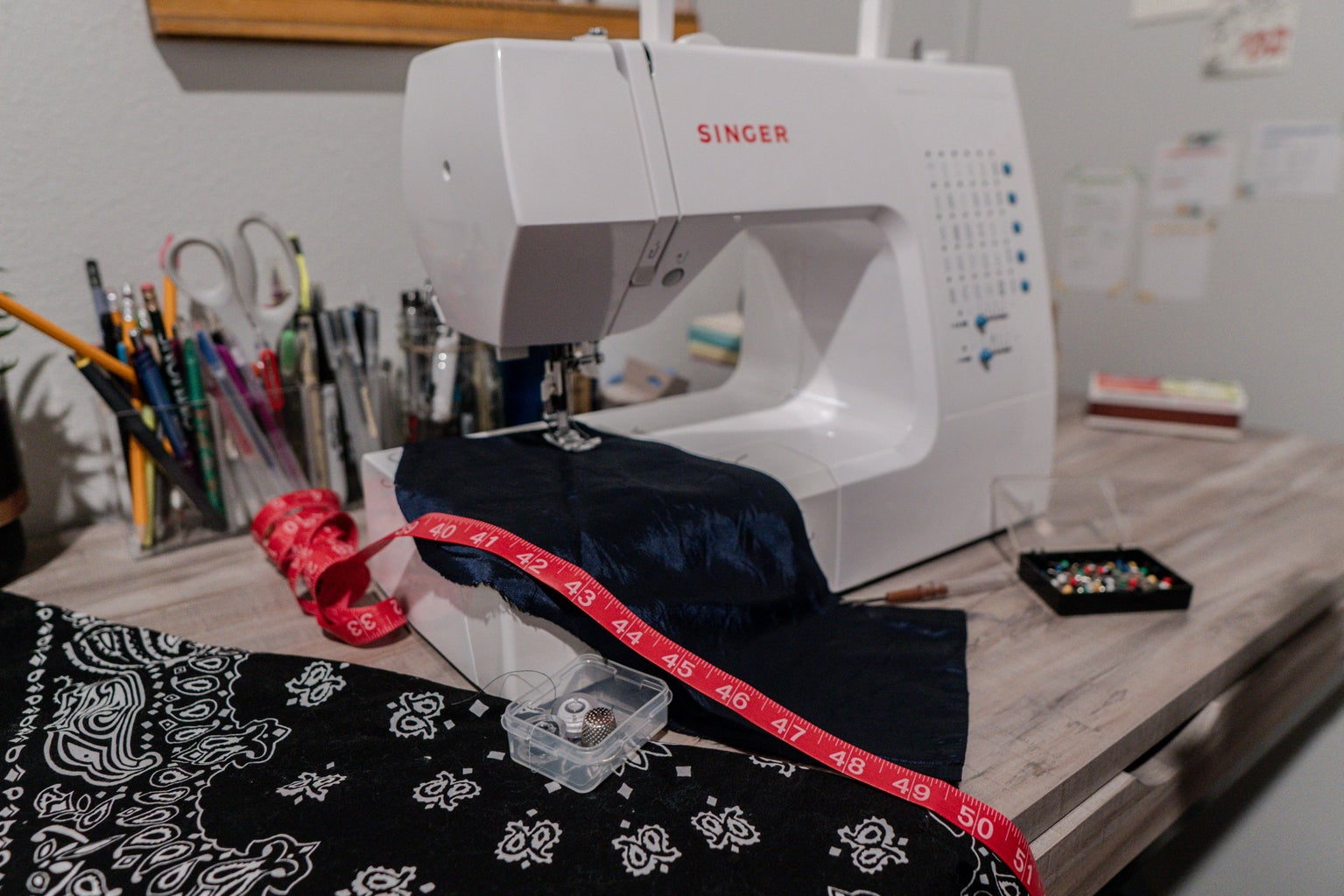 sewing machine with pink measuring tape and blue fabric