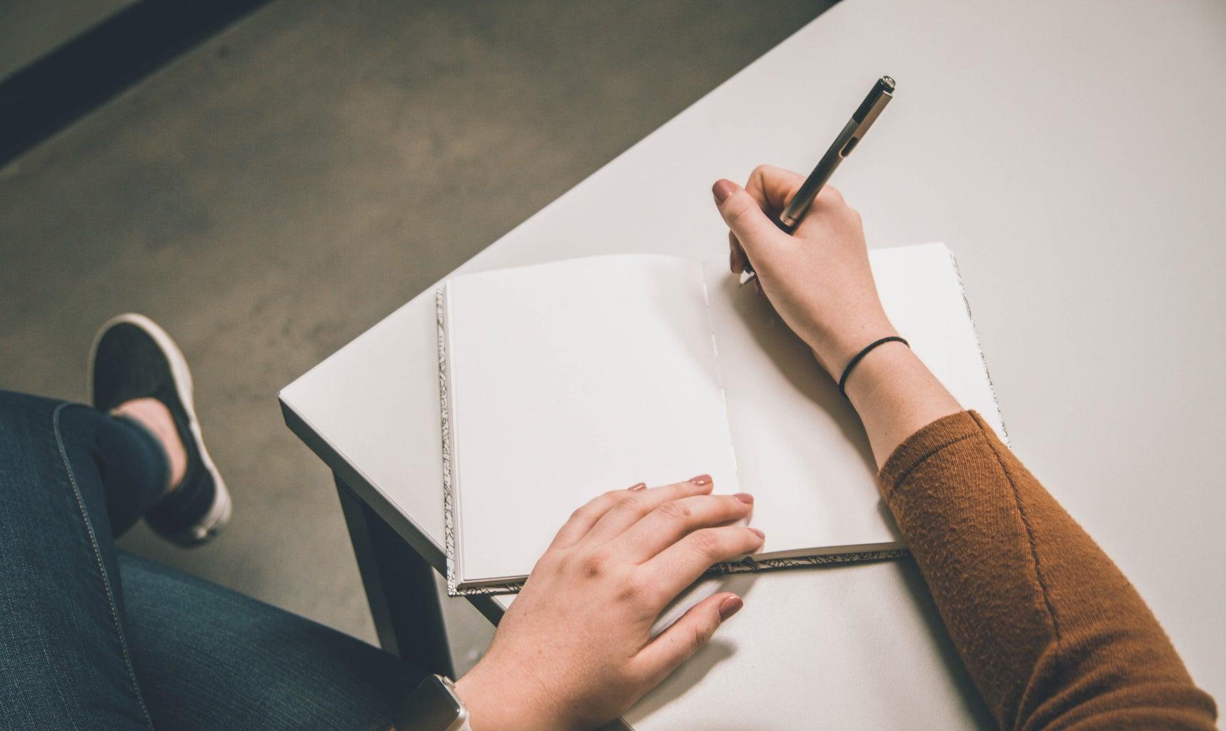 writing in journal on desk