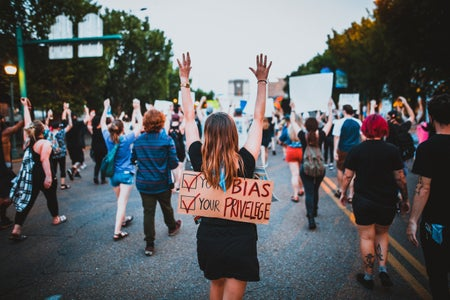 people walking at a protest, focus on one woman that has a sign on her back and her hands up