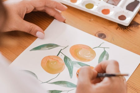person painting oranges using watercolor