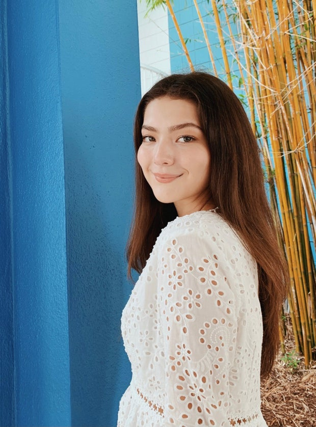Juliana Simone Carrasco white shirt, brown hair, blue background.