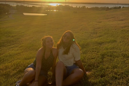 Two girls sitting by sunset