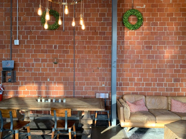 Brick wall, wreaths, hanging lights, table/chairs (CxT 2)