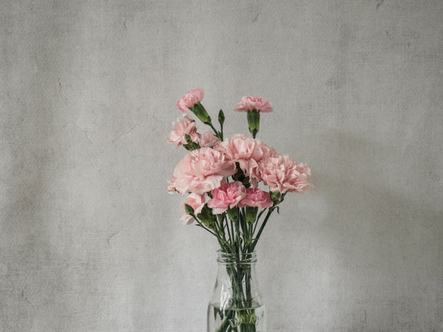pink carnations in a clear glass bottle