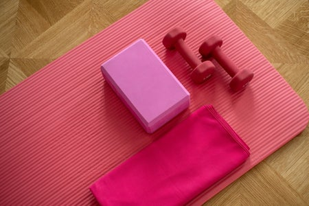 pink yoga mat with two pink weights and other exercise equipment