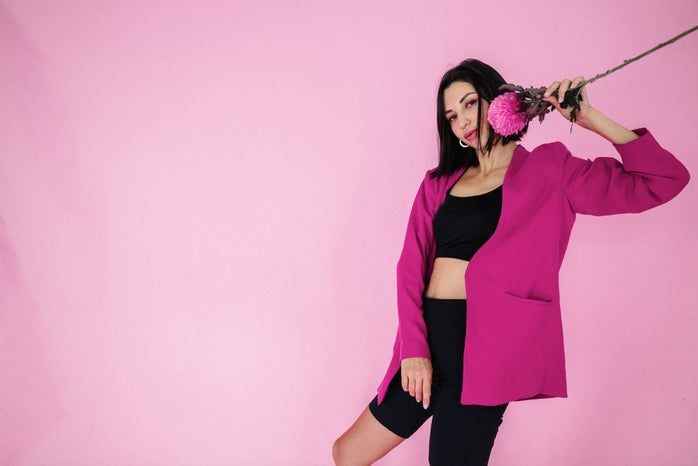 woman in pink blazer holding a flower