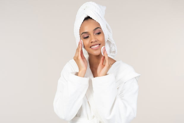 woman in robe and towel wiping face