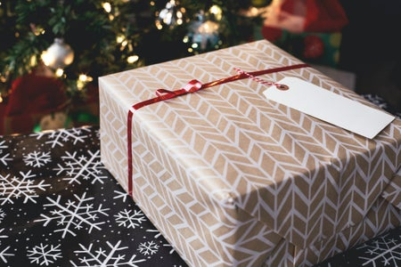 Gold and white gift box on black and white far-isle print surface