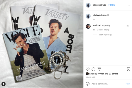 Image of magazines with Harry Styles on the cover laid out on a bed with accessories