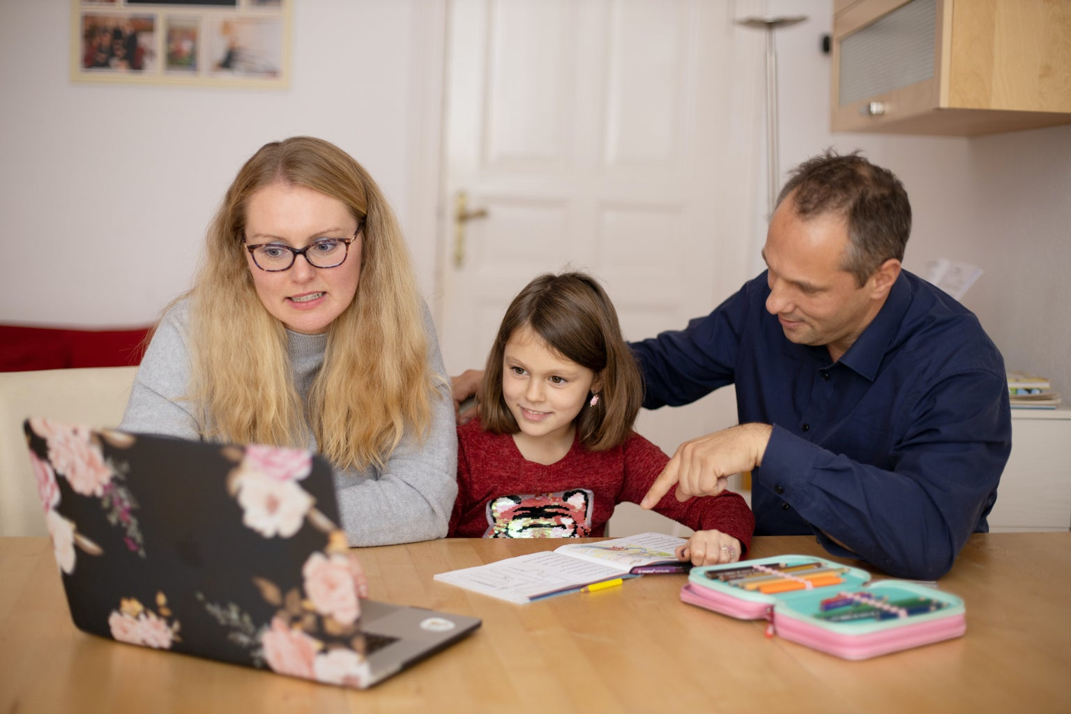 Parents helping their daughter with her homework at the kitchen table.