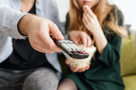 man holding remote, sitting on couch with woman, popcorn