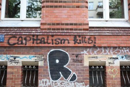 "brown brick building ""capitalism kills!"" graffiti"