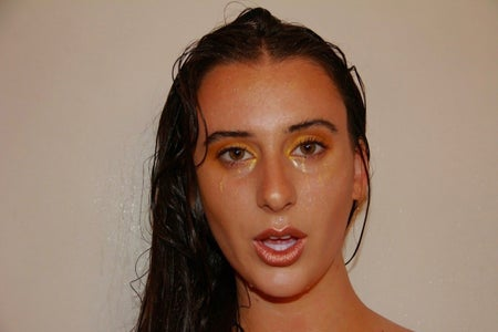 woman staring at the camera with gold makeup and her mouth slightly open